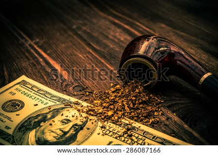 Tube for smoking tobacco and money on a wooden table. Image vignetting and the orange-blue toning - stock photo