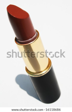 Tube of maroon lipstick against white background - stock photo
