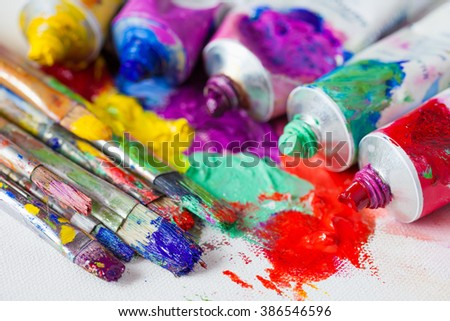 Tubes of multicolor oil paint and artist paintbrushes on canvas closeup. - stock photo