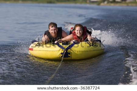 Tubing fun on the lake - stock photo