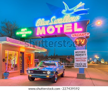 TUCUMCARI, NM/USA - MAY 9, 2013: Dusk at the historic Blue Swallow motel on Route 66. A classic car is parked under the iconic neon sign. - stock photo