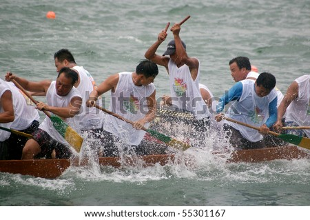 TUEN MUN, HONG KONG -  JUNE 16: Participants paddle their boat during a dragon boat race on June 16, 2010 in Tuen Mun, Hong Kong - stock photo