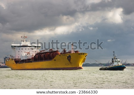 Tug and tanker are leaving the harbour - stock photo