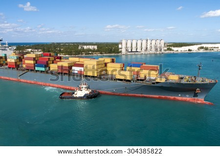 Tug Boat assisting a contain tanker in to an industrial port - stock photo