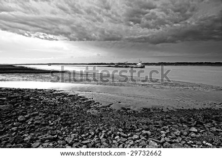 tug boat going by during angry weather at low tide - stock photo