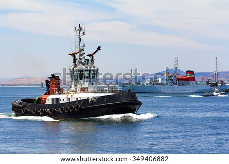 tug boat in harbor steaming through the water with ships in the background - stock photo