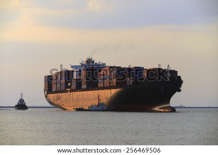 Tug boat pulling out container ship - stock photo