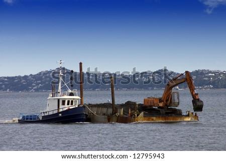 Tug boat pushing dredging barge - stock photo