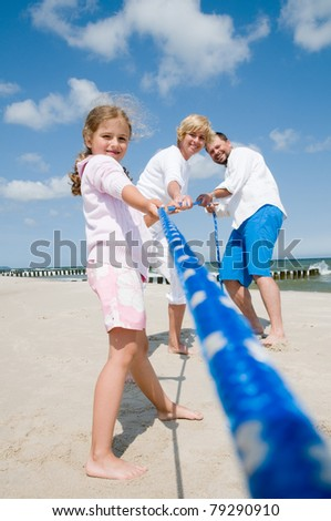 Tug of war - family playing on the beach - stock photo