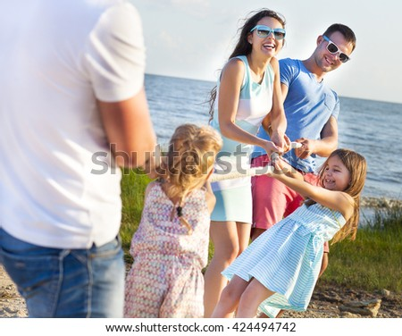 Tug of war - family playing on the beach. Summer holiday and family power concept