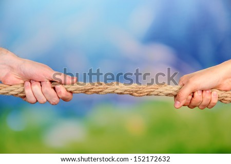 Tug of war, on bright background - stock photo