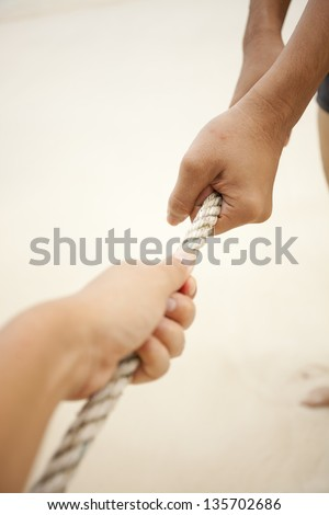 Tug of war, two sides of hand pulling rope to oneself - stock photo