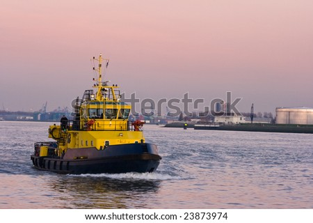 Tug passing by at sunset on the river - stock photo