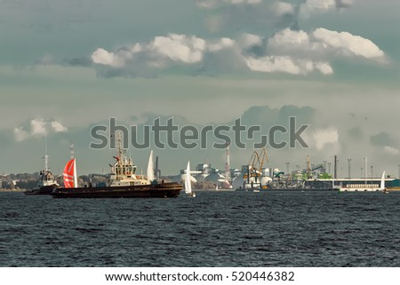 Tug ships and sailboats against cargo terminal in Riga