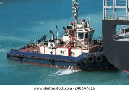 Tugboat assisting a large tanker ship in to or out of port - stock photo