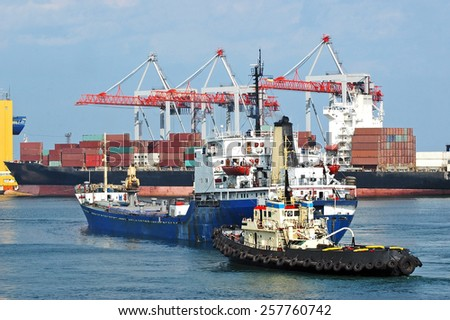 Tugboat assisting bulk cargo ship to harbor quayside - stock photo