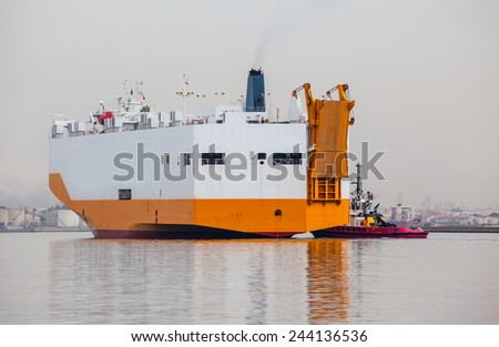 tugboat pulling a cargo ship away from the dock  - stock photo
