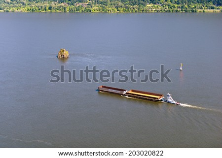 Tugboat pushing barge carrying cargo on the Columbia River and swims near the cliffs located in the midst of the river, on the shore strip located green trees. View from above. - stock photo
