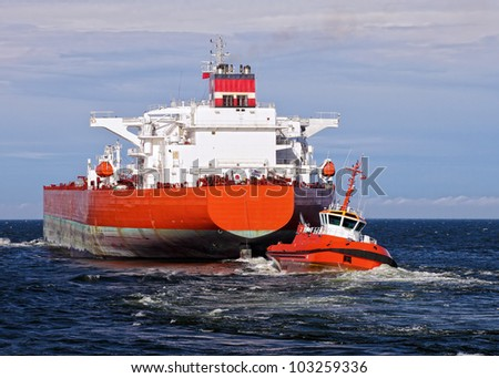 Tugboat towing a large cargo ship in port. - stock photo