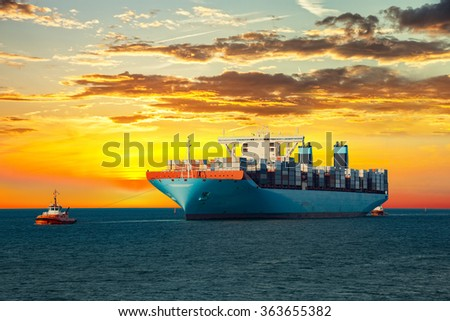 Tugboats assisting container ship on sea in the morning. - stock photo