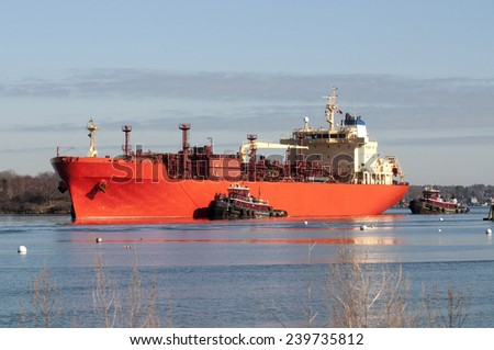 Tugboats guide a ship into Portsmouth Harbor in New Hampshire. - stock photo