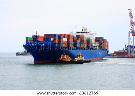 tugboats pulling  container vessel - stock photo