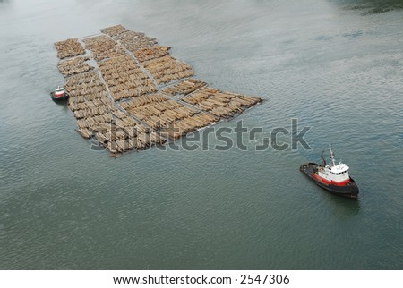 Tugboats pulling log boom - stock photo
