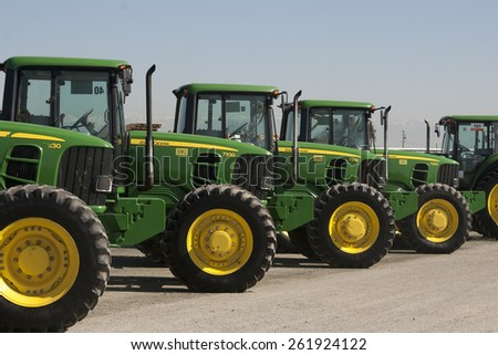Tulare, CA, USA - February 11, 2011: A row of John Deere tractors ready for a California agricultural auction. - stock photo