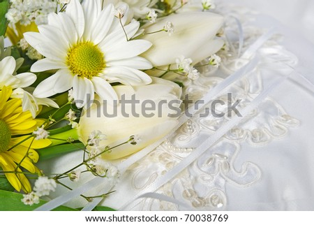 tulip and daisy wedding bouquet on satin pillow - stock photo