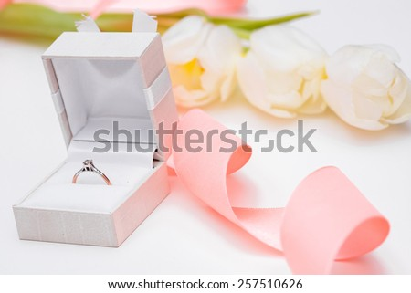 tulip and gold engagement ring on a white background  - stock photo