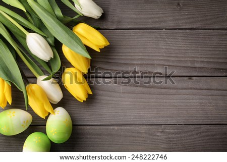 Tulips and easter eggs on wood background - stock photo