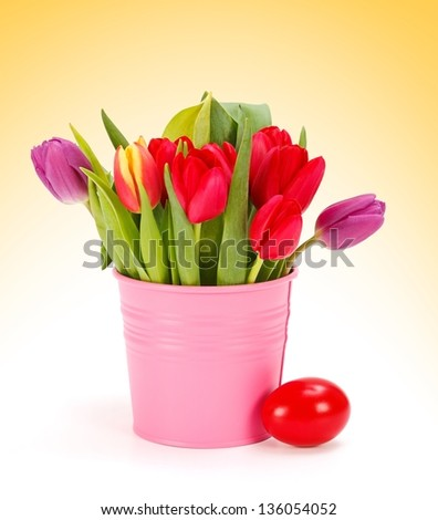 Tulips in pink bucket and a shiny red Easter egg