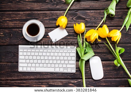 Tulips, keyboard and office supplies on a wooden board. View from above - stock photo