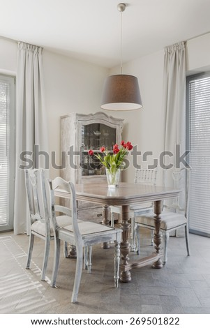 Tulips on the table in retro dining room - stock photo