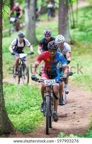 TULLINGE, STOCKHOLM - JUNE 8: Group of mountain bike cyclists thru a forest trail at Lida loop race 2014 during a sunny day in the Swedish nature. June 8, 2014 in Stockholm, Sweden.
