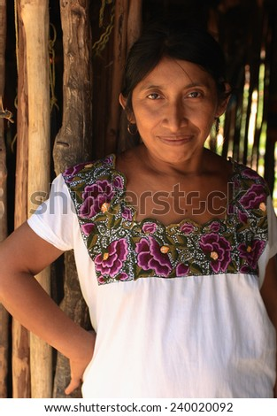 TULUM, MEXICO - NOVEMBER 24: An unknown Mayan woman in typical dress poses in front of her home. On November 24, 2006 in Tres Reyes, Tulum, Mexico. - stock photo