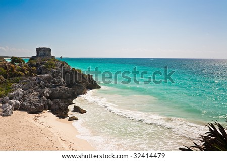 Tulum, Mexico, with Mayan ruins (El Castillo) visible on the cliffs overlooking the water. - stock photo