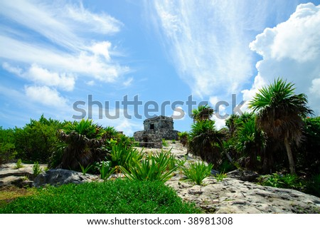 Tulum relic and temple standing in a bright green lawn against a cloudy sunny sky made up of multiple white patterns of cumulus clouds - stock photo