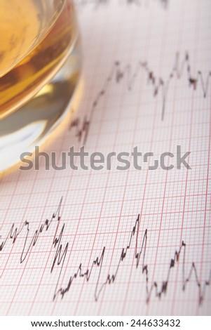 Tumbler Of Alcohol On ECG Printout - stock photo