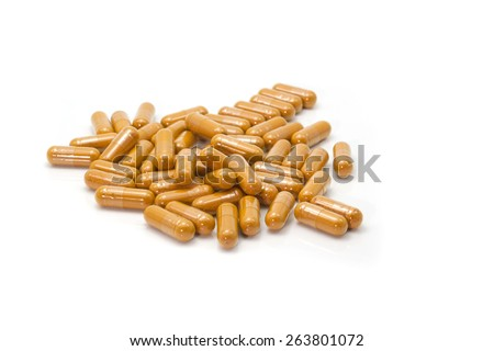 Tumeric powder capsules on white background - stock photo