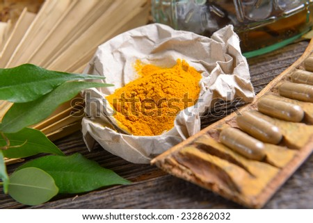 Tumeric powder spice on wooden board with tabletes as healthy supplement of diet - stock photo