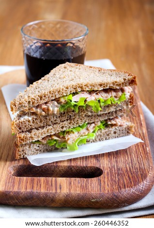 Tuna and brown bread sandwiches on board - stock photo
