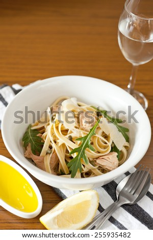 Tuna and caper spaghetti pasta with rocket and shaved Parmesan. Served with lemon, olive oil and a glass of white wine on a blue and white table cloth with a silver fork and spoon cutlery. - stock photo