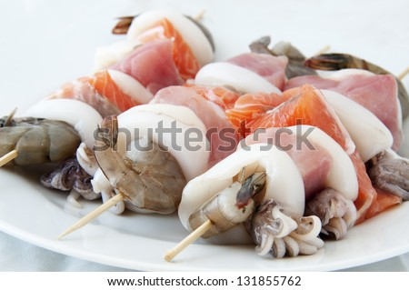 Tuna and salmon skewers with prawns and squid - stock photo
