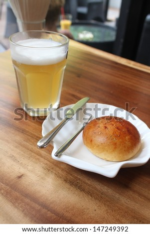 Tuna bun and a glass of beer - stock photo