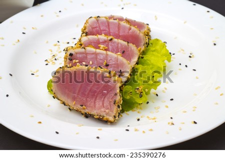 Tuna fillet with sesame on a big white plate over black background - stock photo