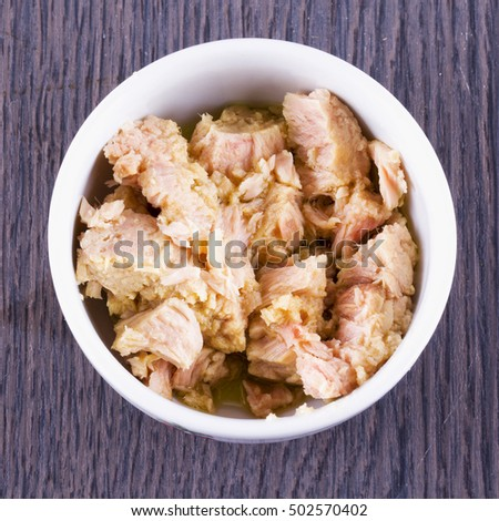 Tuna in pieces in white cup, square image