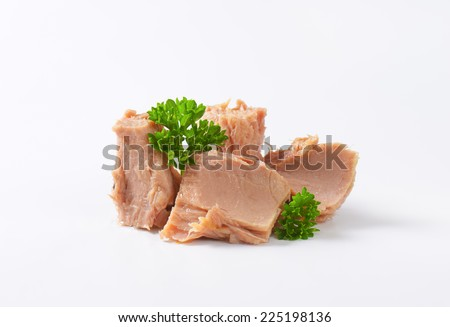 tuna meat with fresh parsley on white background - stock photo