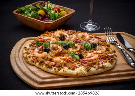 Tuna pizza with shrimp and salad, cutlery, close up - stock photo