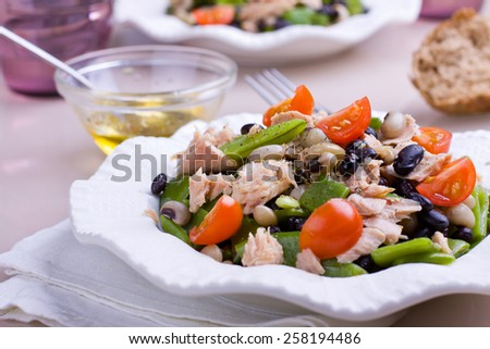 Tuna salad with green, black and white beans garnished with fresh cherry tomatoes  - stock photo